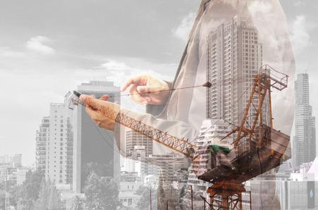 exposicion: Doble exposición del hombre y de la grúa de poder en la ciudad como concepto Construcition Proyecto. Foto de archivo