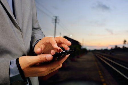 businessman waiting call: Business Man using mobile phone on empty railway platform, Close-up hands, as Wireless Communication concept. Stock Photo