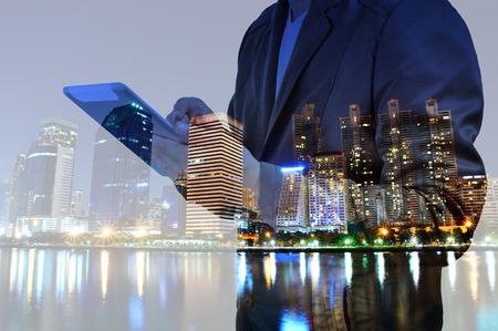 exposicion: Doble exposición de la Ciudad de la noche y hombre de negocios usando un dispositivo de tableta digital como concepto de desarrollo de negocios. Foto de archivo