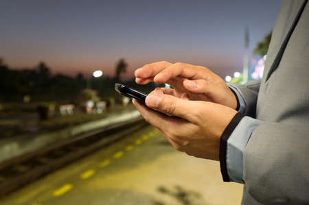 businessman waiting call: Business Man use Mobile Phone in Railway Station at Dawn Stock Photo