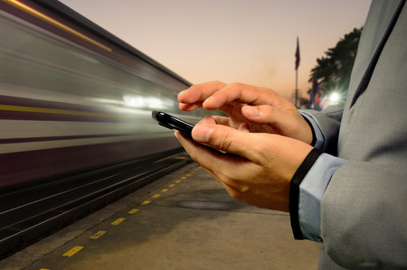 phone business: Business Man use Mobile Phone in Railway Station at Dawn with High Speed running Train