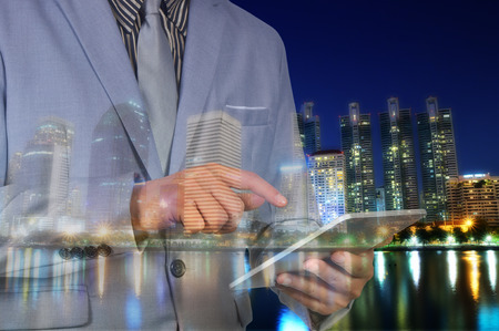 digital device: Double exposure of Night city and business man using digital tablet device as Business development concept. Stock Photo