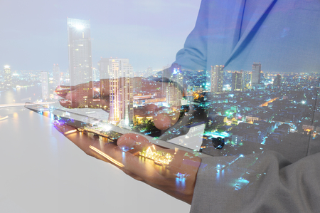 Double Exposure of Business Man using Mobile Tablet and City at Twilight as Global communication concept