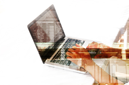 return trip: Double exposure of Business Man use Notebook with Airport Scene and Flight Schedule as Air Booking or Business Travel concept. Stock Photo
