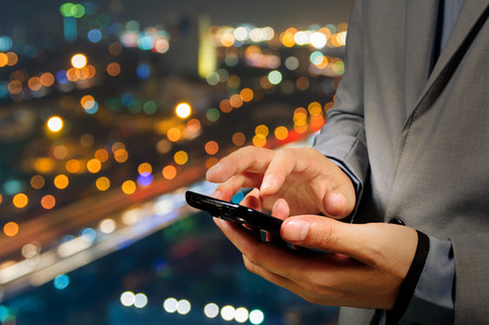 Handsome Business male in the city using his smartphone with Bokeh Background Stock Photo