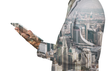 over white: Double exposure of a businessman and a city using a tablet over white background