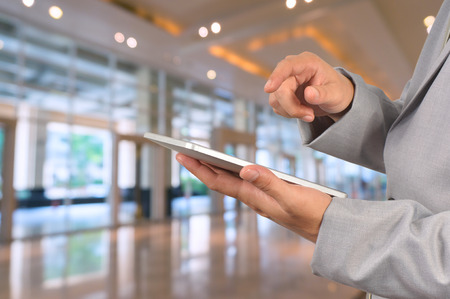 Young Businessman using tablet standing in office, Hotel Lobby or Ballroom. Stock Photo