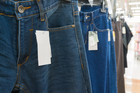 outlet store: Blank White Tag over the Blue Jeans on Hanger Shelf in Supermarket or Hypermarket Retail Outlet Store, Shallow Depth of Field Stock Photo