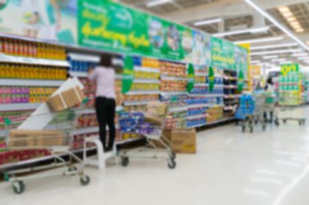 rearrangement: Merchandising. Sales assistant in supermarket arrange goods on supermarket shelves at store, Abstract Blur or Defocus Background