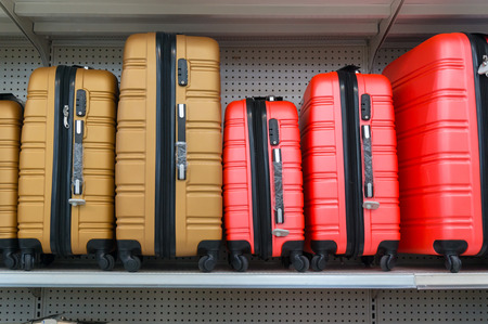 store shelf: Yellow and Red Suitcases in a Row on Shelf in Supermarket Retail Store outlet Stock Photo