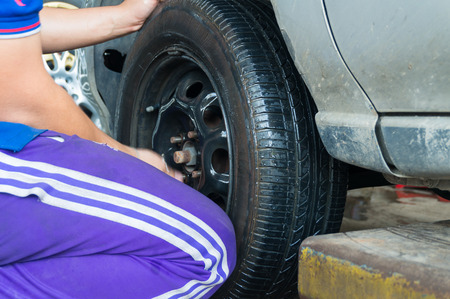 unscrewing: Man Changing Tire by turning Wheel Nut and Bolt with hand, Motion Blur. Stock Photo