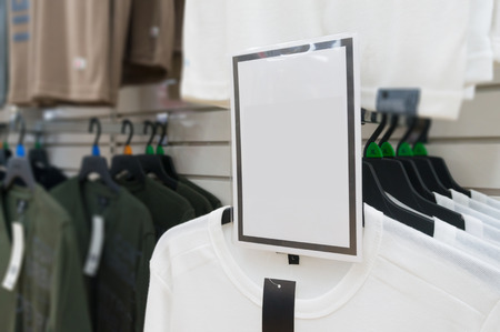 sellout: Blank White Tag or Sign over White t-Shirt on Hanger Shelf in Supermarket or Hypermarket Retail outlet, Shallow Depth of Field Stock Photo