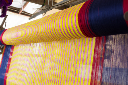 Yellow, red and Blue Color Silk Line.  Yarn pattern is set up on the loom bench and ready to weave.