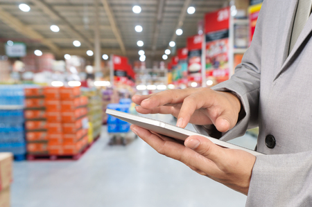 Hand of Businessman, Manger use Mobile Tablet in supermarket with Blur Background of product display on shelves in Supermarket or Hypermarket warehouse Zdjęcie Seryjne