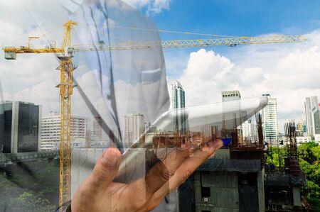 Doble exposición del ingeniero de negocios mantenga Wireless PC tableta digital y resumen de la ciudad como concepto industrial de la construcción