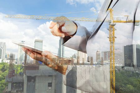 young engineer: Double exposure of business engineer Hold Wireless Digital Tablet PC and abstract city as Construction industrial concept