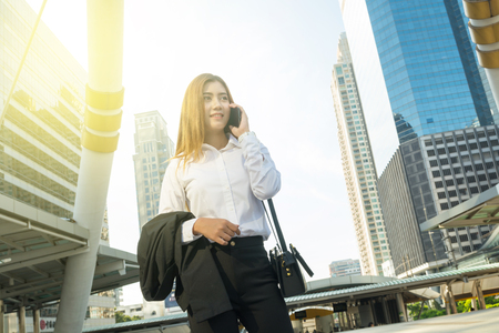 woman business suit: Asian Business Woman use Wireless Smartphone in Modern City as Digital Technology Concept