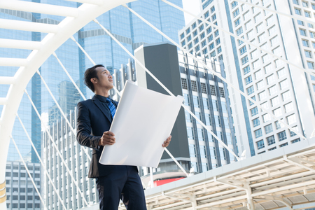 Businessman or Architect Survey or Inspection New Project Progress While Working at Constructions Site as Real Estate Development Concept. Stock Photo
