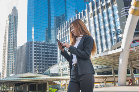 Asian Business Woman use Wireless Smartphone in Modern City as Digital Technology Concept. Stock Photo