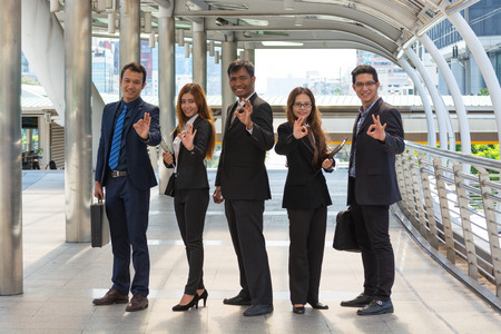 Energetic Young Businesspeople, three businessmen and two Businesswomen showing ok symbol Stock Photo - 71866496