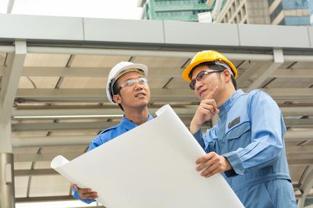 Zwei Ingenieur oder Architekt diskutieren über moderne Bauvorhaben auf Baustelle in städtische Stadt
