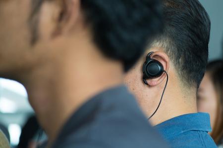 国際ビジネス会議やセミナー オンライン通訳または翻訳通訳システムの一部としてのヘッドフォンを着用で男性の観客