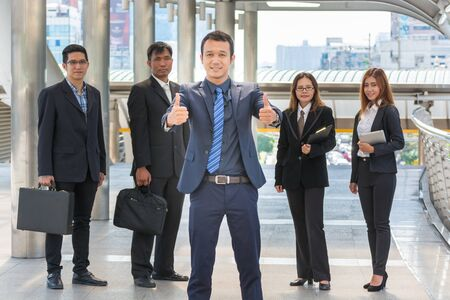 Smiling and Confident Asian Business Team Standing in Modern City Environment and Building as Successful Business Concept photo