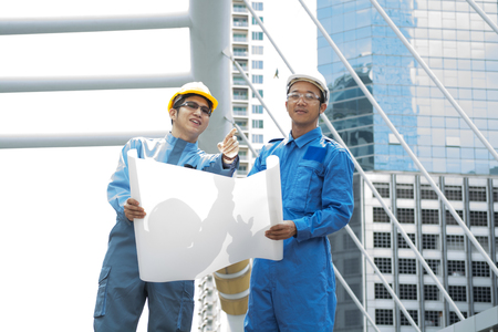 Two Engineer or Architect discuss on Modern Building Project at Construction site in Urban City photo
