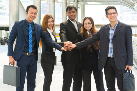 Asian Business Team showing Unity with their hands together as Business Teamwork Concept photo