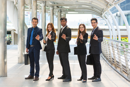 Energetic Young Businesspeople, three businessmen and two Businesswomen showing ok symbol like thumbs up, smiling and posing for camera near business center. As group Teamwork or Team Success Concept photo