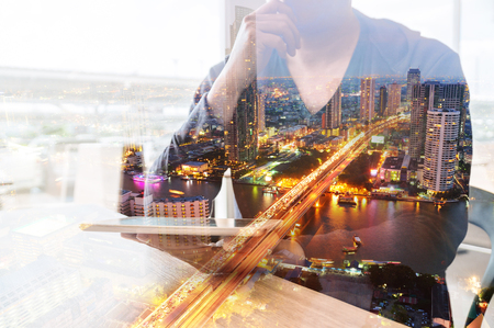 Double Exposure of Man or Male hold Digital Wireless Smart Tablet with City Building Business Street and Bridge as High Speed Data Technology Innovation Networking and Real Estate ProJect Development Concept. Stock Photo