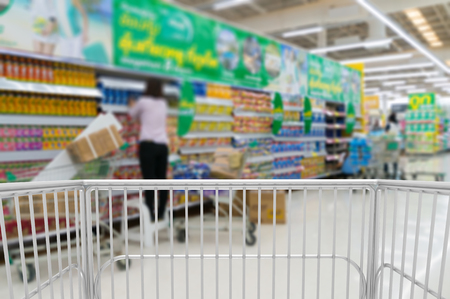 Trolley Shopping Kart with Blur Bokeh Background of Merchandising or Sales assistant in supermarket arrange goods on shelves at Hypermarket or Convenience store Outlet. Stock Photo