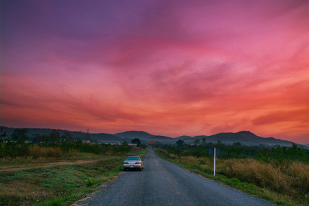 Car drive on Country Road to Door of Cemetery  with Colorful Morning Sky in Mountain of Pakchong, Nakhon Ratchasima Thailand as Fantasy Journey to Door of Heaven or Amazing Place Concept