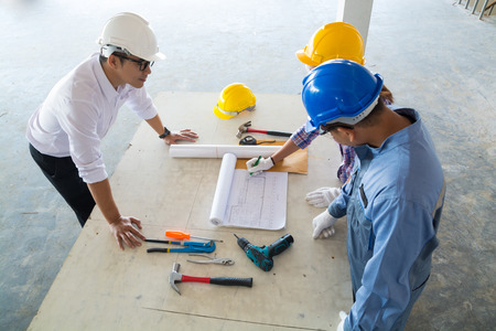 Bauteam, Architekt, Ingenieur und Vorarbeiter, die im Hochbaustandort als Real Estate Project Development Concept sich besprechen