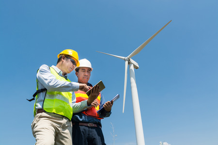 Alternative Power or Renewable Energy Technology Project Development Concept, Engineer and Architect discuss over Digital Wireless Tablet and Clipboard while working at Wind Turbine Power Generator Tower site.