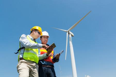 Projektentwicklungskonzept für alternative Energie oder Technologie für erneuerbare Energien, Ingenieur und Architekt diskutieren über digitale drahtlose Tablets und Zwischenablagen, während sie am Standort des Windkraftanlagen-Stromerzeugerturms arbeiten.