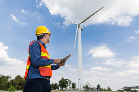 Electric Engineer use Digital Wireless Tablet Device with Wind turbine power Generator Tower Background as Green energy or Renewable Energy Technology Project Development Concept.