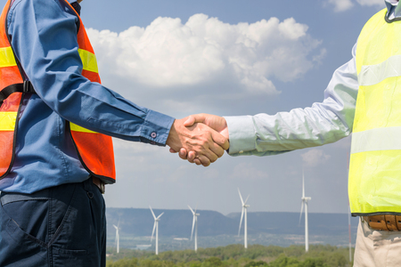 Architect and Engineer shake hand beside wind Turbine Power Generator Field as Project Development Company Agreement Joint Venture concept.