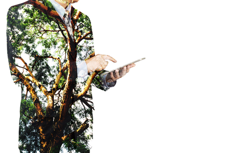 Double Exposure of Businessman use Digital Wireless Tablet with Tree and Branch as Business CSR or Technology with Nature Conservation and Freedom Think Concept.  Zdjęcie Seryjne