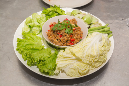 Spicy pork chops chilli dip with Fresh Long bean, Eggplant, Lettuce, Sliced Cucumber, White radish and Goa or Wing Bean, Thai Popular Food eat with Steamed Rice