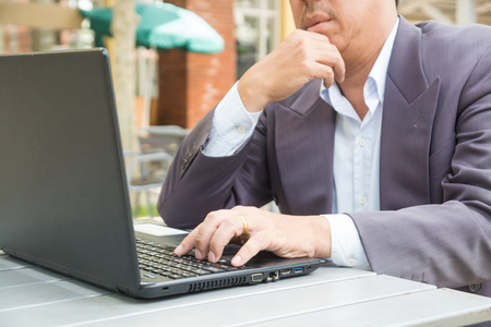 Hand of Businessman typing on Notebook or Laptop Computer on Table in Outdoor Public as Mobile Workplace and Modern Lifestyle Standard-Bild