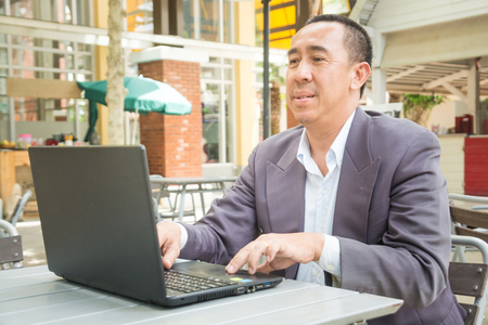 Asian Businessman typing on Notebook or Laptop Computer on Table in Outdoor Public as Mobile Workplace and Modern Lifestyle Standard-Bild