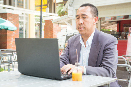 Asian Businessman typing on Notebook or Laptop Computer on Table in Outdoor Public as Mobile Workplace and Modern Lifestyle Zdjęcie Seryjne