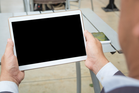 Asian Businessman in Suit use Digital Wireless Tablet outdoor in Public with Wifi connection as Modern Business and Technology Lifestyle Standard-Bild