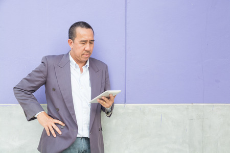 Asian Businessman use Digital Wireless Tablet Computer while Standing or Leaning against violet Color Concrete Wall as Modern Technology and Business Lifestyle