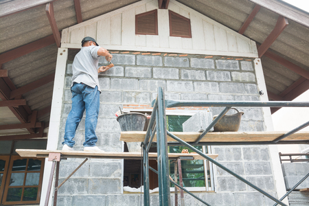 Male or Man Worker or Laborer working with Cement Block to Build Wall of Home or House as Construction Business Industrial Concept.