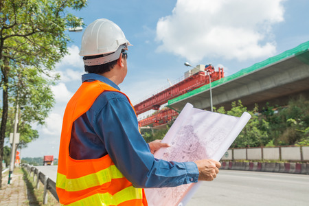 Engineer or Architect wear white Helmet working or reading Construction Plan in Highway or Autobahn Construction site as Industrial or infrastructure Contractor Concept. Standard-Bild