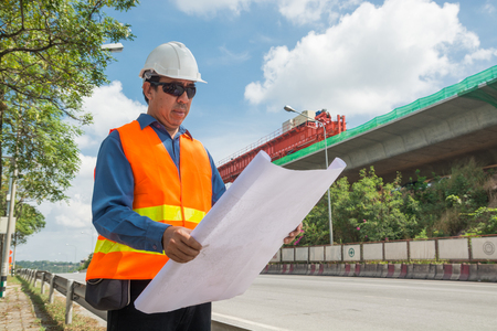 Engineer or Architect wear white Helmet working or reading Construction Plan in Highway or Autobahn Construction site as Industrial or infrastructure Contractor Concept. Zdjęcie Seryjne