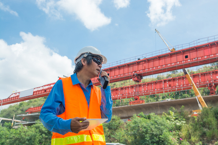 Architect or Engineer, wearing white Hardhat and safety vest, use Radio Communication to supervise Motorway Project Development as Infrastructure Construction Industrial concept.
