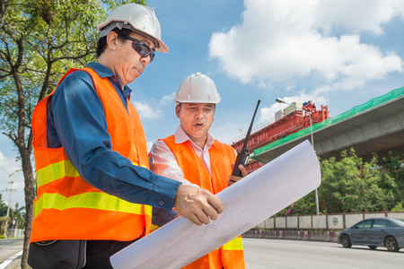 Engineer and Architect or Foreman wear white hardhat and Glow safety cloth meeting in construction site and control Highway Project Development as heavy industrial concept. Zdjęcie Seryjne